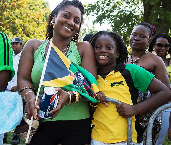 Little boy with dreads wearing I LOVE JAMAICA shirt standing with his mom.