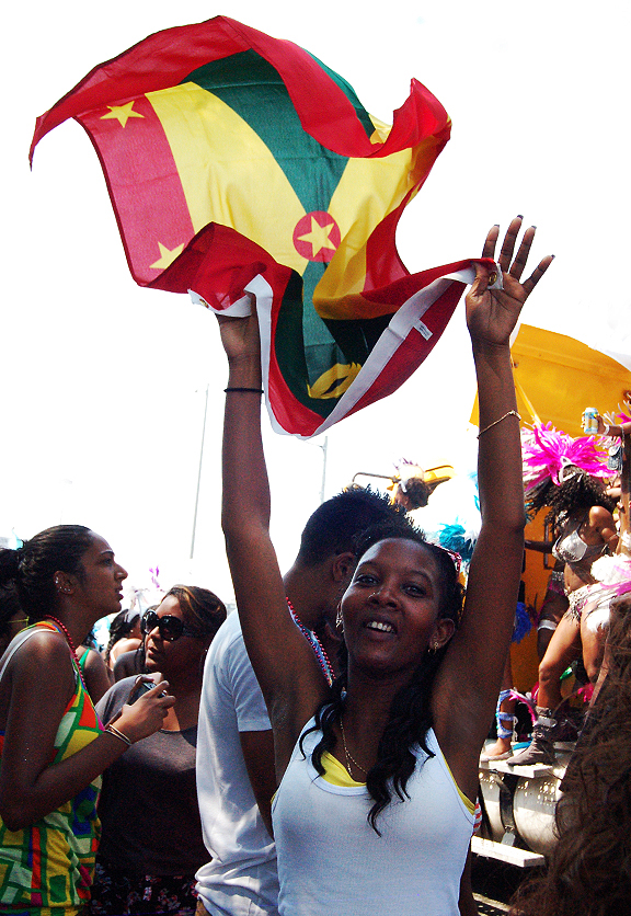 Young woman waving the flag of Grenada