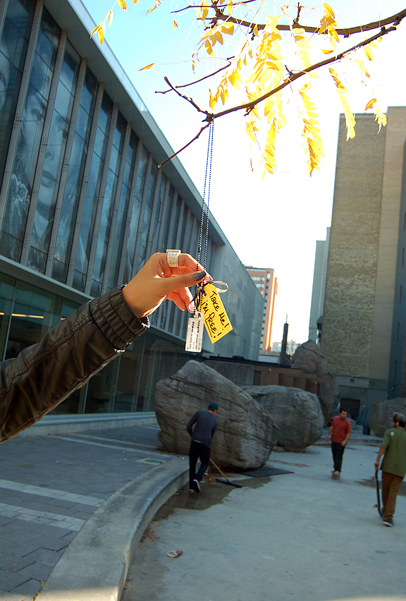 Hanging a necklace up in front of Image Arts Building, Ryerson University, Toronto.