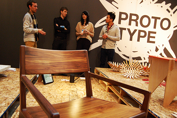 Close up of a dark wood chair, people standing behing it talking