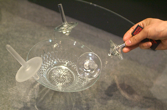 Man spinning glass tops made from up-cycled stemware with frosted finish