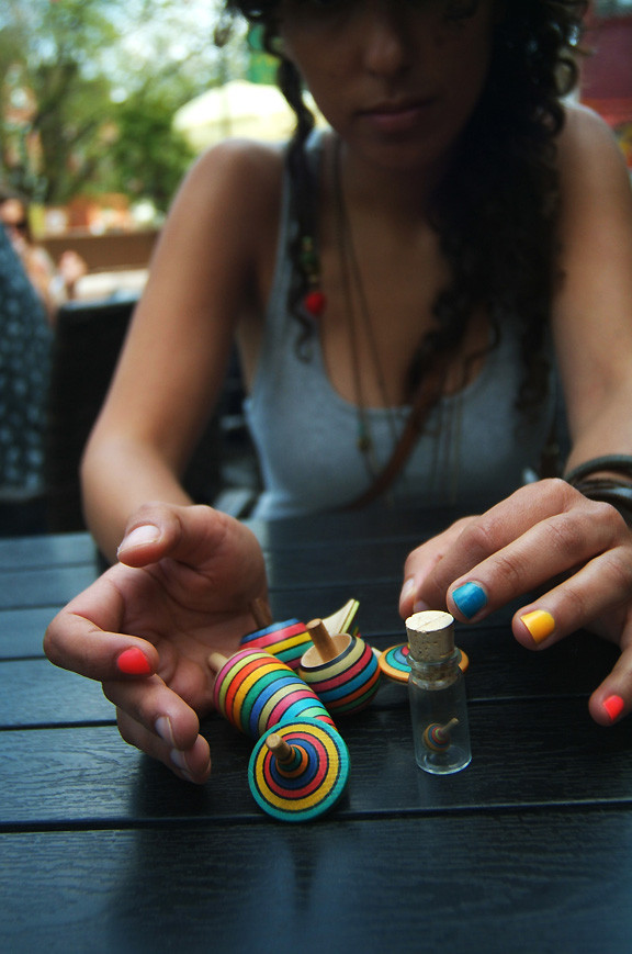 Woman playing with spinning tops on a table