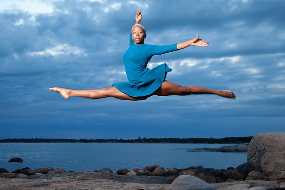 Female dancer leaping into air on beach with water and rocks behind her