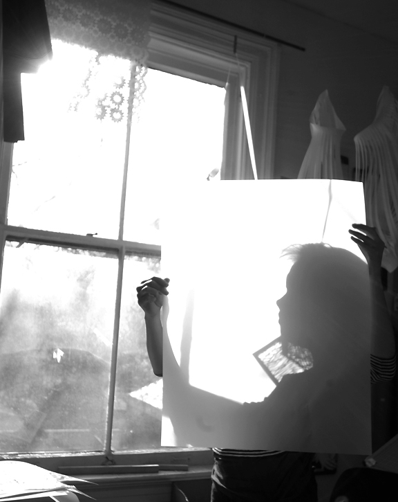 Woman holding up a piece of paper like a veil with her profile as a shadow behind