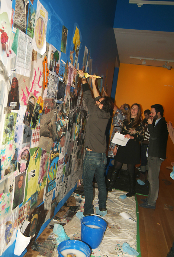 People putting up collage on wall with paste in buckets