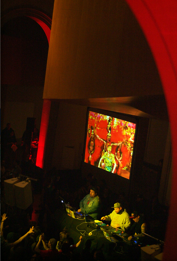 3 male deejays performing with turntables and screen behind them with reappropriated and remixed images of Native Americans