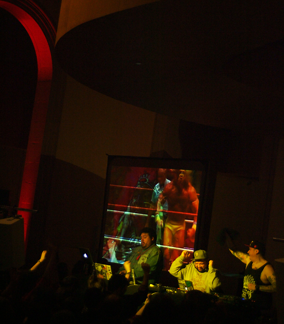 3 male deejays performing with turntables and screen behind them with re-appropriated and remixed images of Native Americans and First Nations people.
