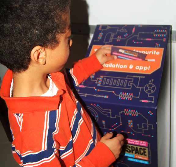 Young boy casting a ballot in a box to vote for his favourite exhibit at DigiPlaySpace