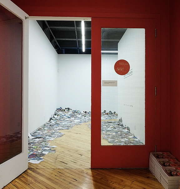 Office door opening to large mounds of small photographs piled for gallery installation