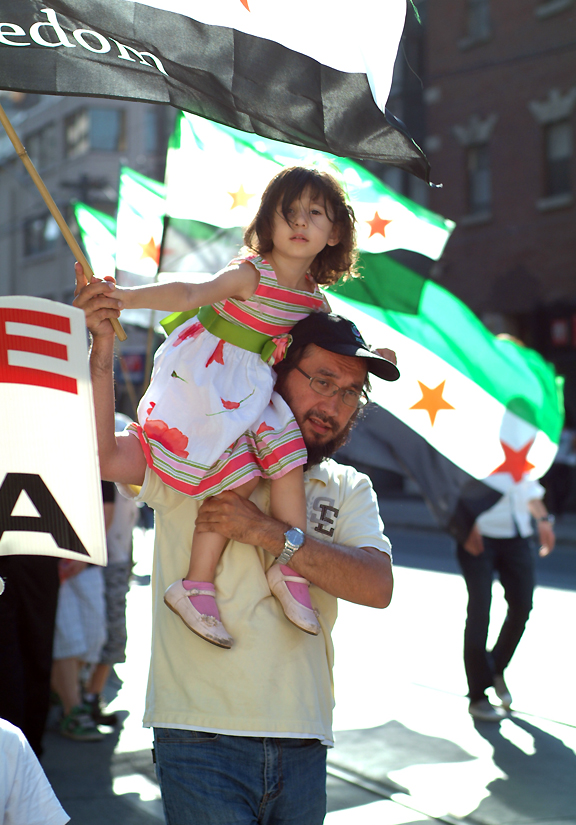 Little girl sitting on her father's shoulders during a protest on Syria, holding a flag with message FREEDOM with more flags in backbround.