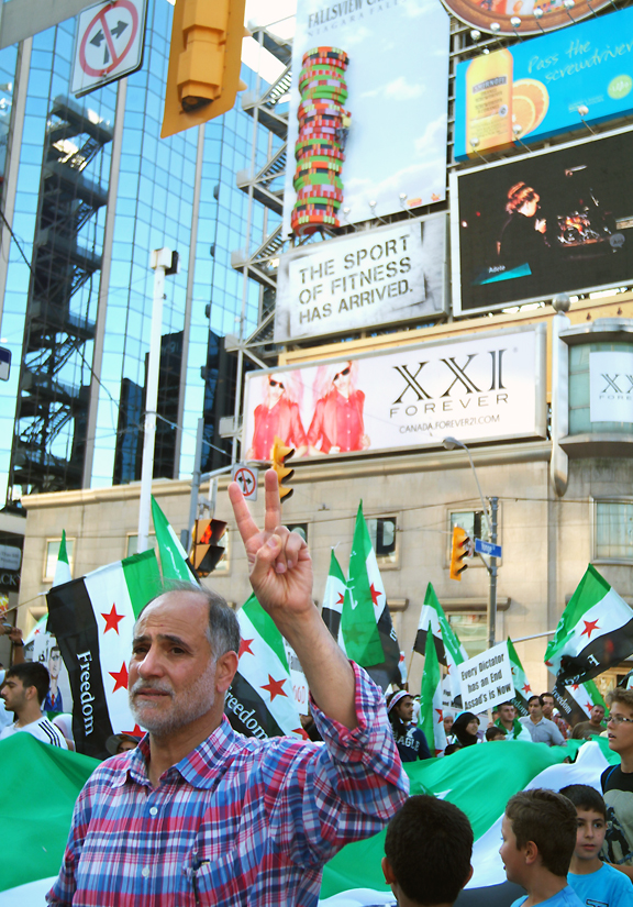 Older man raises his hand in peace symbol, young boys in behind him holding giant Syrian FREEDOM flag like a blanket.
