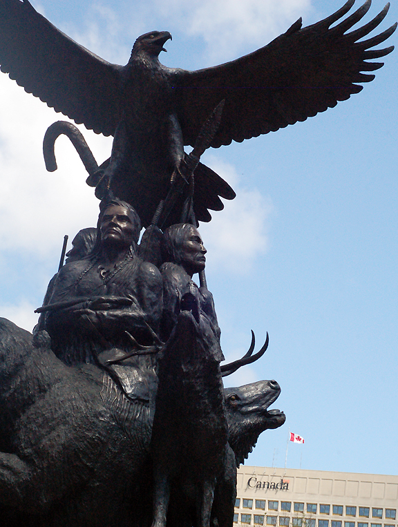Metal sculpture of native men in traditional attire with eagle spanning wings above their heads, wolf at their feet and building with Canada written on it in the background.