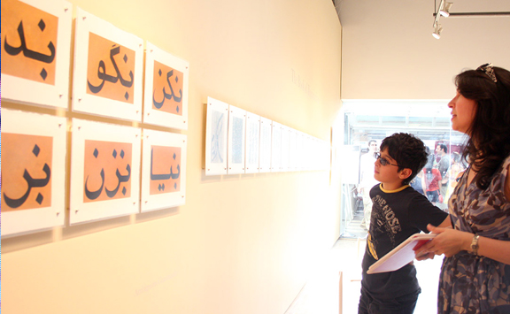 Mother and son looking at images of art incorporating Farsi script