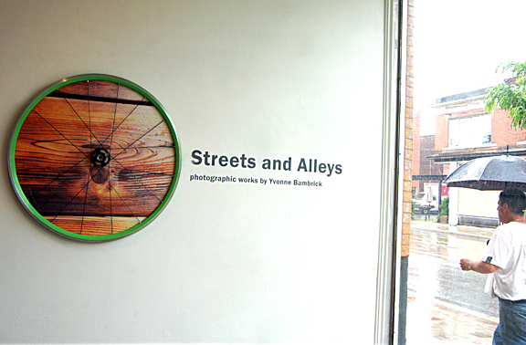 photograph framed in a bike wheel on wall with window to the street on the right