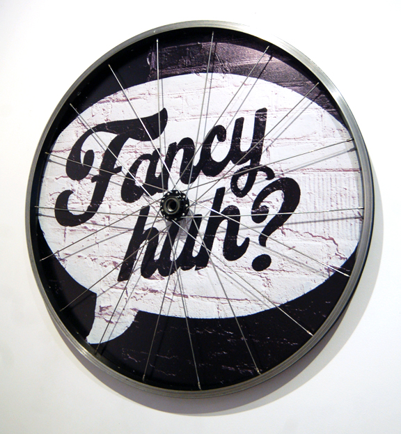 A photograph of graffiti with words Fancy Eh and framed in a bike wheel