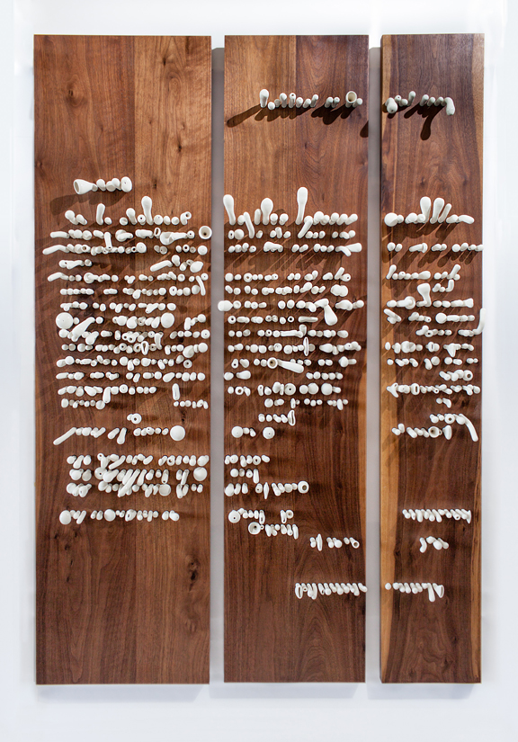 Small organically shaped white porcelain shapes placed into 3 panels of wood hanging on a wall