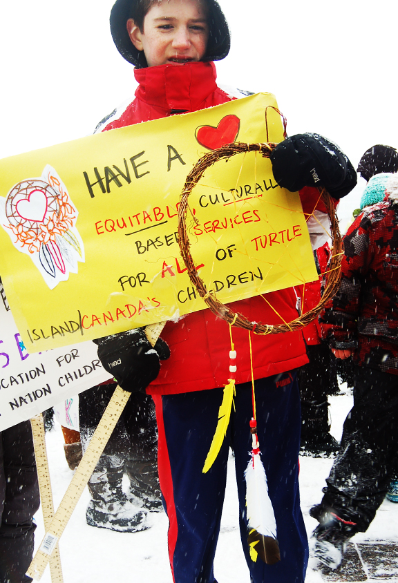 Boy in snow holding poster that saves Have A Heart for first nations children