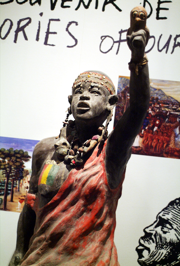 Statue of a woman warrior with words Guinea on her breast to represent Africa, one arm raised in a salut.