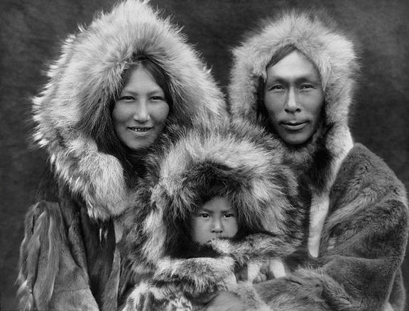 Antique image of Inuit family, mother, little child and father with traditional clothing