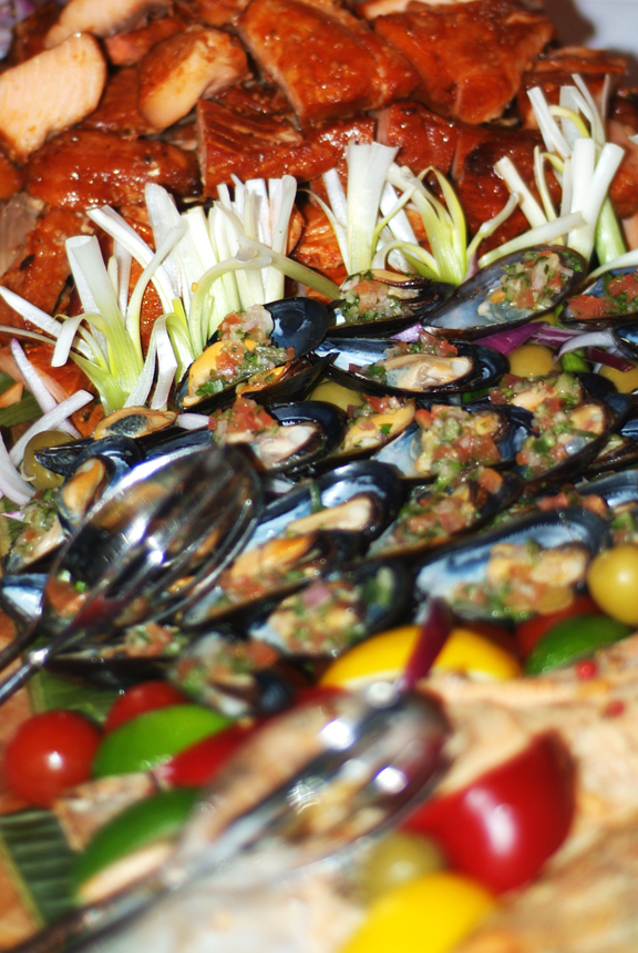 Close up of plate of food full of smoked fish and mussels