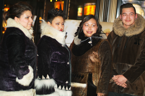 Young Inuit men and women modelling sealskin jackets