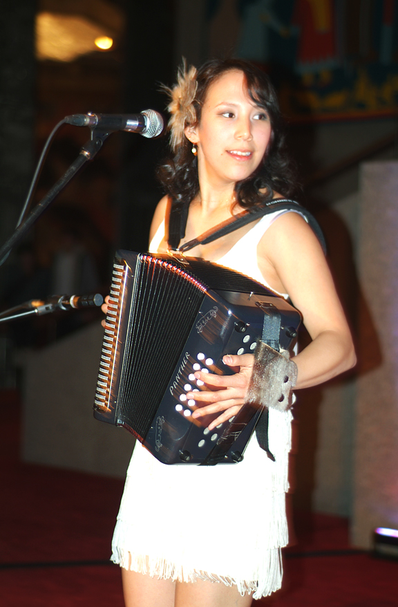 Young Inuk woman playing accordian