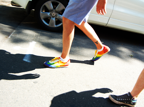 two guys walking, only see their shows and legs, one guy is wearing rainbow coloured running shoes