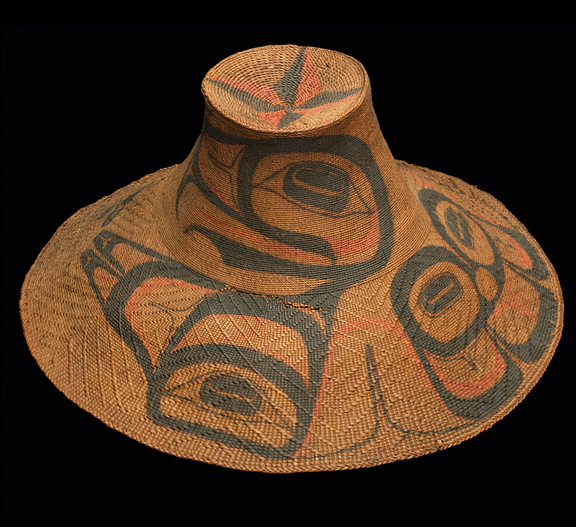 A wide brimmed hat woven out of spruce root and painted in Haida designs
