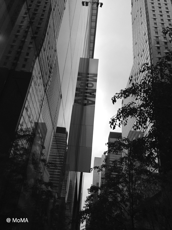 looking up at tall skyscrapers with sign on one that reads MOMA