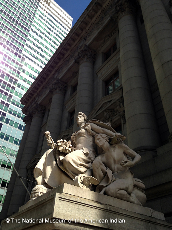Large stone sculpture of woman and man with larger classic style building and skyscraper behind it