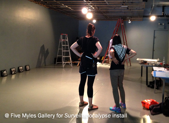 two women stand with back to the camera looking at a gallery with an installation in progress, ladders, tables