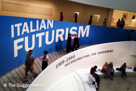 inside the Guggenheim Museum with people sitting in the centre area and the words Italian Futurism on the wall