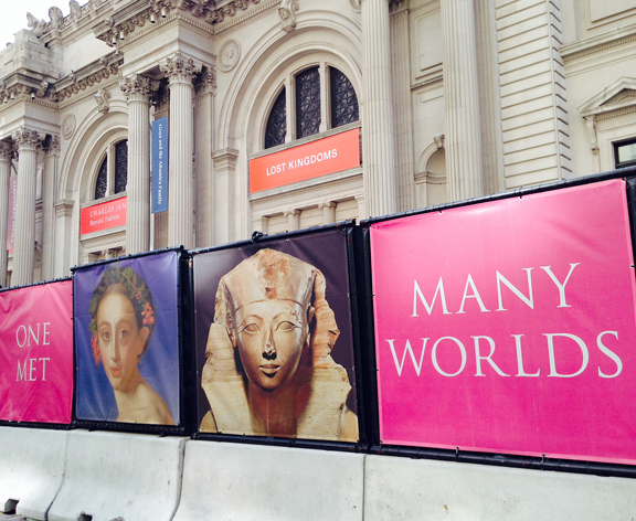 Advertising for the Met with painting of white woman and photograph of a pharaoh on right. Words One Met Many Worlds on the posters.