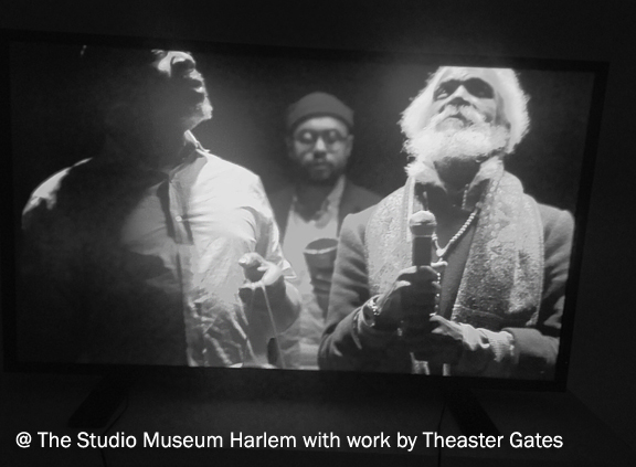 Photograph of a tv screen with video of 3 black men singing and performing. The ages of the 3 men vary from middle age to old
