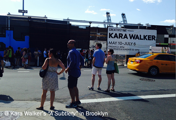 Street scene in an industrial area, people waiting at the corner, poster that reads Kara Walker