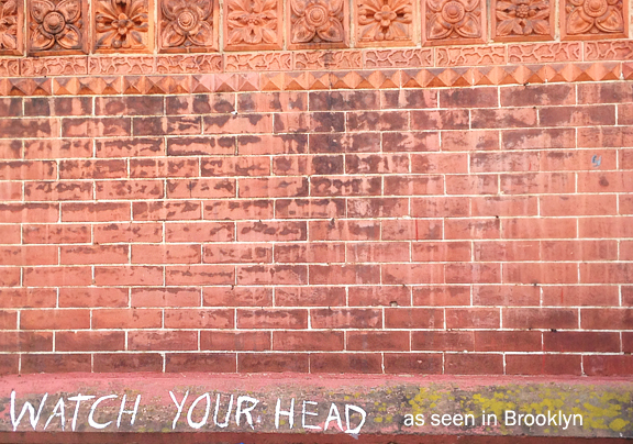 Brick work and ornate decorative patterns carved in stone and white text painted that reads Watch Your Head