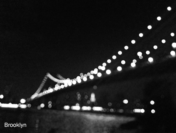 A bridge at night, lined with lights that are out of focus.