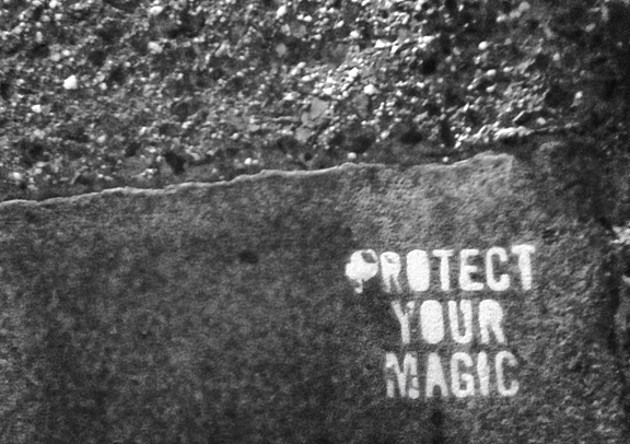 stone and pavement on a street with the words Protect Your Magic painted on it