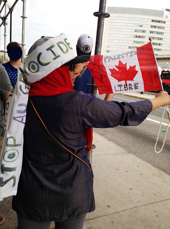 Woman in hijab with head scarf around hijab that reads Stop the Genocide and holding Canadian Flag that says Free Palestine.