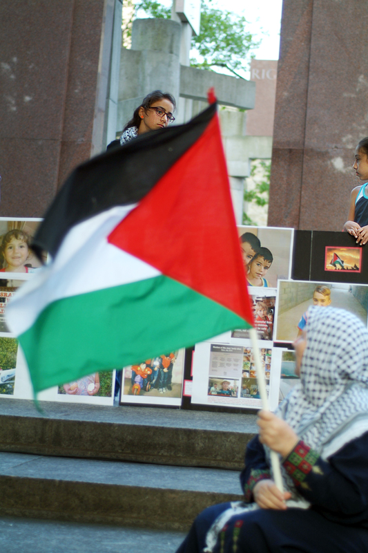Old woman on steps of Human Rights Monument holds waving Palestinian flag, posters of dead children behind her