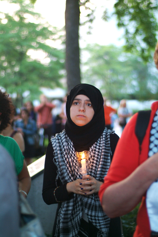 Young woman a keffiyeh hijab holds a candle and listens
