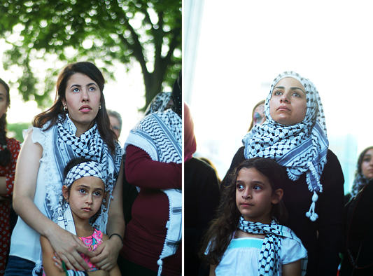 Two young woman hold small girls close to them as they listen to the ceremony. Each woman and girl wears a keffiyeh