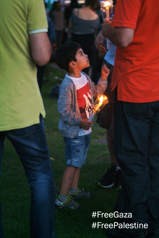 Little boy in running shoes and shorts holds a candle, he points up to an adult man above him also holding a candle