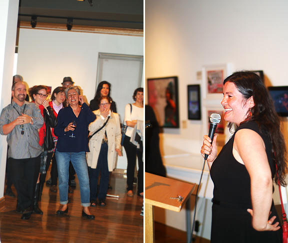Crowd of people with artist in middle, curator at the microphone smiling