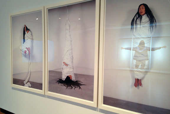 Series of 3 photographs of woman wrapped in white linen like a mummy but with head hanging out. One image she is upside down and hanging