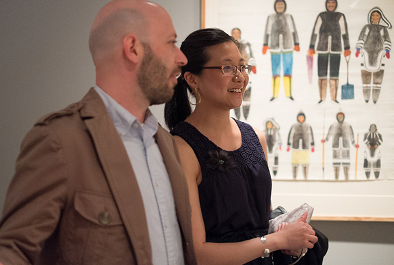 Man and woman in front of Inuit print of people in traditional dress