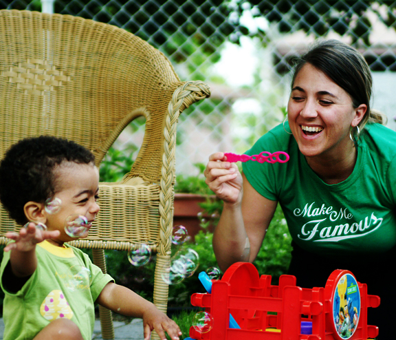 woman blowing bubbles with little boy
