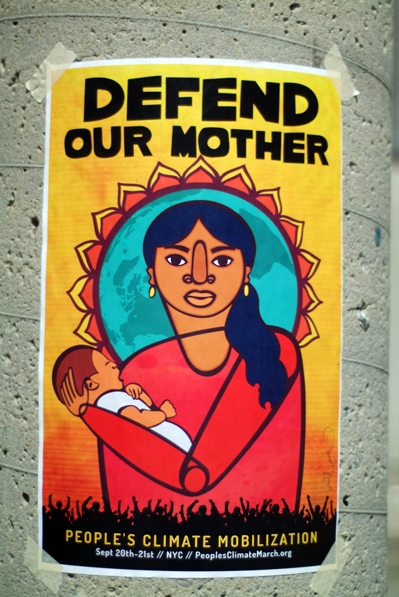 Poster on pole that says Defend Our Mother and has a colourful print of a woman holding a child.