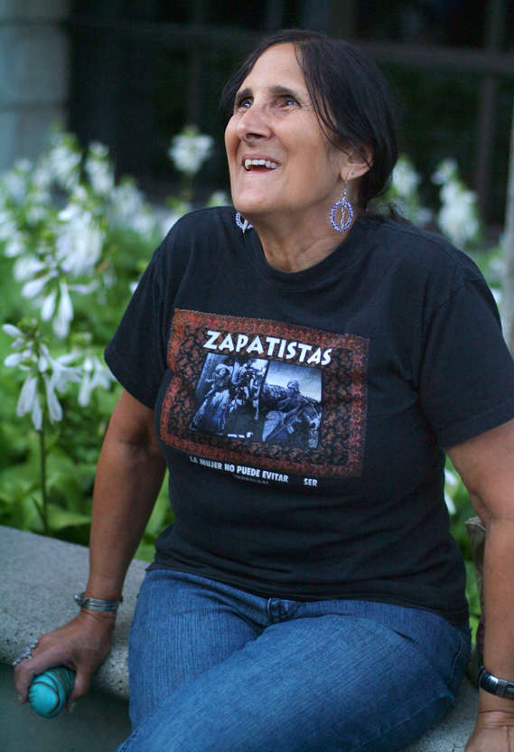 Woman sitting wearing a t-shirt that says Zapatistas