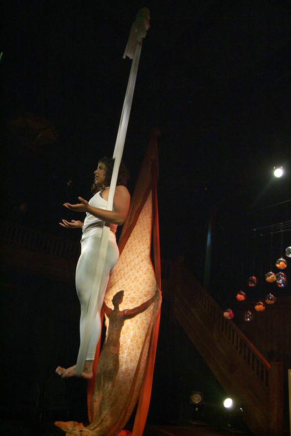Two young East Asian woman, one hanging from fabric suspended from ceiling the other backlit behind a sari suspended